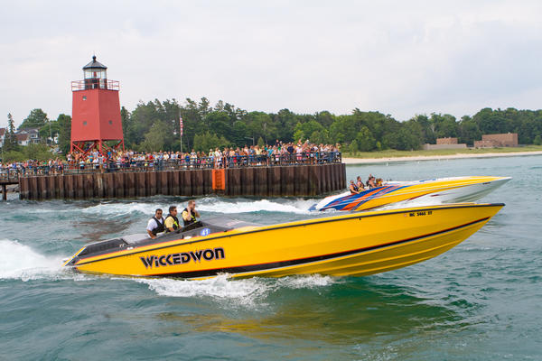 Crowds of spectators line the Pine River Canal to watch a fleet of race boats slow to no-wake speeds as they participate in the Boyne Thunder poker run last year between Boyne City and Charlevoix.