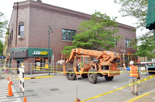 Crews, on Tuesday, unload material and scaffolding that will be used to repair damaged brickwork at the top of the Masonic Building in downtown Charlevoix.