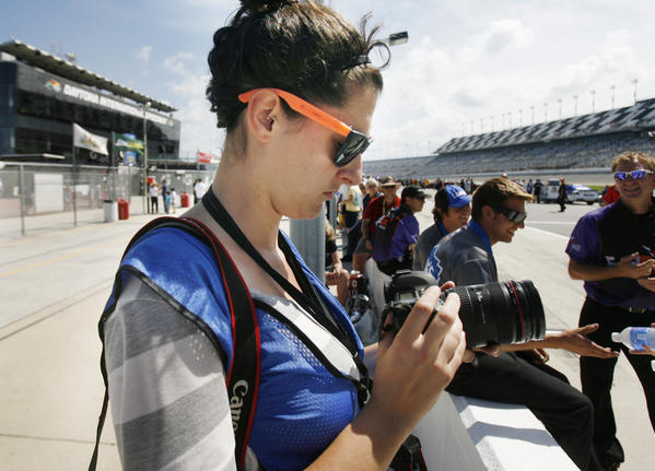 Orlando Sentinel photo intern Megan May checks her camera settings during qualifying for the Coke Zero 400 Sprint Cup race at Daytona International Speedway.