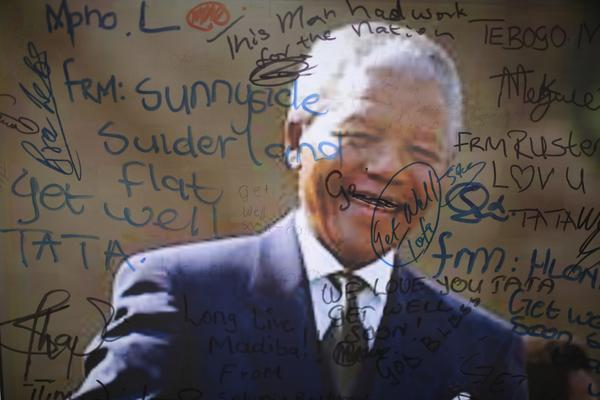 An image of former South African President Nelson Mandela on the wall of the Medi-Clinic Heart Hospital in Pretoria is covered with goodwill messages.