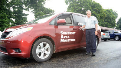 The Rev. Charles Olson and one of the Somerset Area Ministries vans.
