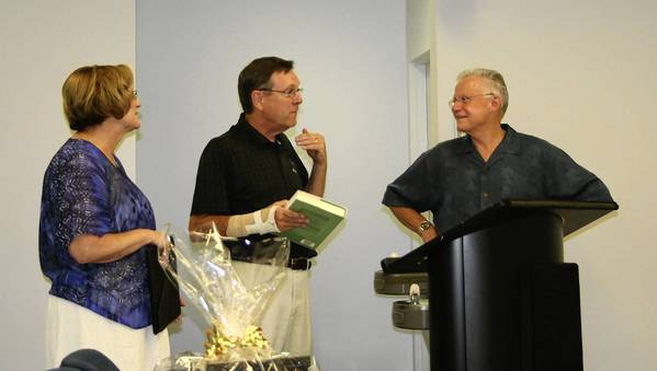 "Kevin Egan, who retired last month after 16 years on the Frankfort Village Board, gives the book ""Guardians of the Sea"" to Mayor Jim Holland, a veteran of the U.S. Coast Guard. In the foreground is the gift basket the village presented July 8 to Egan and his wife, Betsy, left, in recognition of his service to Frankfort. Egan's successor is expected to be named at the July 22 board meeting."