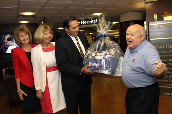 Naperville Mayor George Pradel, right, shows his enthusiasm for the merger of Edward Hospital & Health Services and Elmhurst Memorial Healthcare during a gift presentation to Elmhurst Mayor Steve Morley at Edward Hospital on July 2.