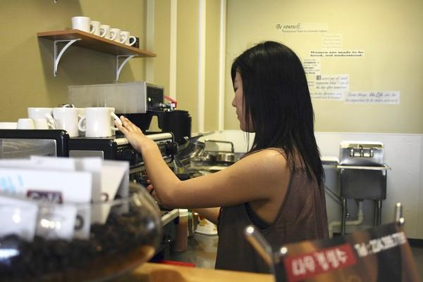 Cafe NaMoo's owner Mindy Sorim Shin prepares coffee for a customer on July 5. The cafe opened up in Glenview at the end of May.
