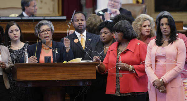 Rep. Senfronia Thompson, D-Houston, second from left, holds a coat hangar as she stands with fellow representatives while proposing an amendment to the second reading of HB 2, legislation that will restrict abortion rights, on the Texas House floor Tuesday in Austin. The Texas House is expected to vote on the bill Tuesday.