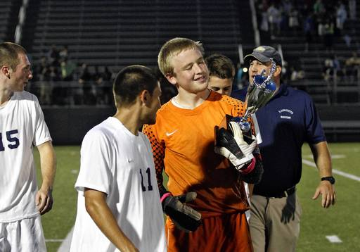 Jonathon Gruenke/Daily Press file photo Lafayette goalie Alex Emerson, right, admires the trophy after defeating Culpeper during Friday's Region I soccer tournament final game.