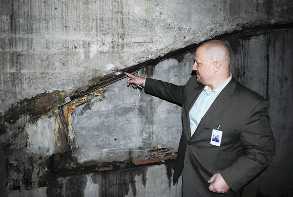 North Shore School District 112 Operations and Facilities Manager John Fuhrer points out crumbling walls in Elm Place School's boiler room during a Jan. 28 tour.