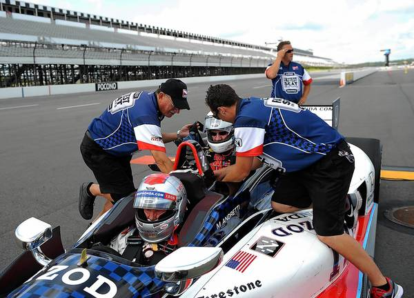 The Morning Call's Keith Groller (back) gets strapped into a two-seat IndyCar with Mario Andretti at Pocono Raceway on Saturday.