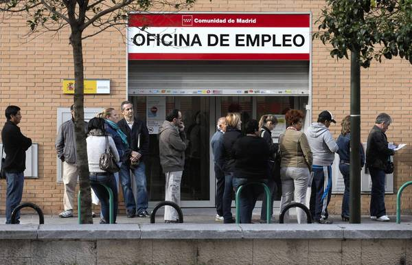 People line up outside an unemployment office in Madrid. The IMF cited the deepening recession in the Eurozone in lowering its U.S. and global economic growth forecasts for this year and next.