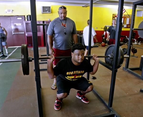 Second-year La Cañada High football Coach James Sims, left, spots his son D'Andre during a squat workout.