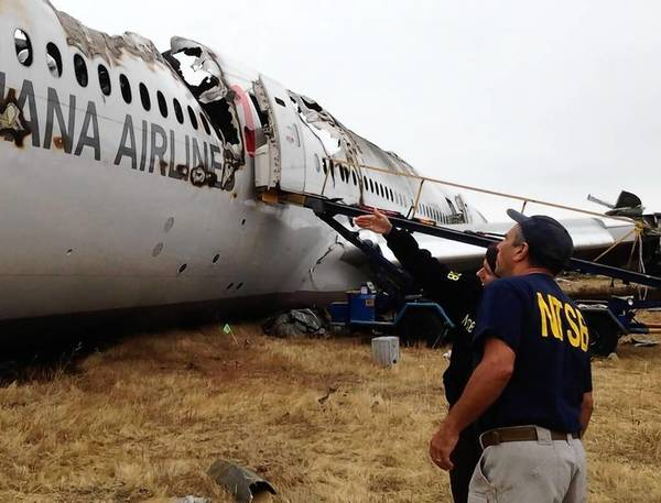 NTSB investigator Bill English and agency Chairwoman Deborah A.P. Hersman examine the wreckage of the Asiana Airlines jet that crashed Saturday in San Francisco.