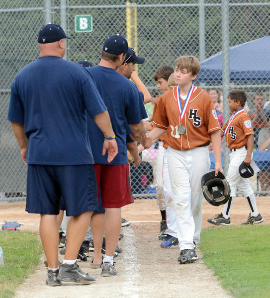 Harbor Springs Majors Division tournament team's Jason Proctor (right) shakes hands with members of the Sault Ste. Marie coaching staff following Harbor's 3-0 loss in the championship game of the District 13 tournament Tuesday at Bates Park.