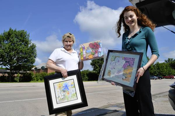 Northbrook Arts Commissioner Julia Miller, left, and Sarah Gianni, Northbrook's summer intern, unload artwork donated by Northbrook artists for the silent auction that will be held as part of the village's Art in the Park event on July 13 and 14.