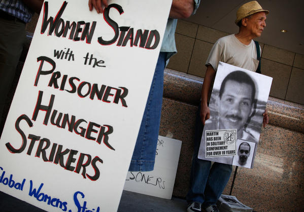 John A. Imani, right, joins about 75 demonstrators Monday in front of the Ronald Reagan State Building in Los Angeles for a rally held in support of Pelican Bay State Prison inmates who are refusing meals in protest of conditions at the prison.