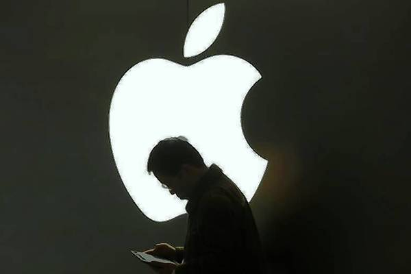 A man looks at his Apple iPad in front an Apple logo in downtown Shanghai.