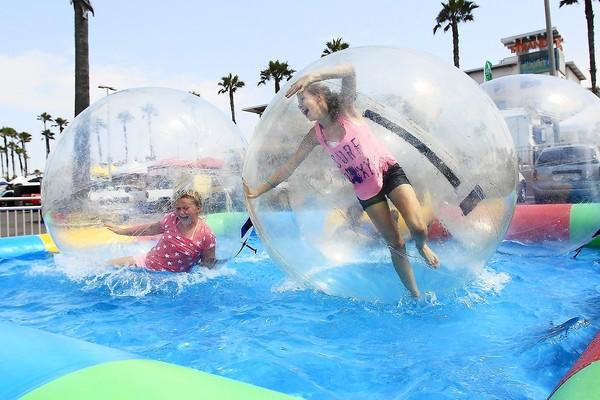 Avery McGlinchey, 10, left, and her sister Riley, 15, try to stay up on their feet as they play around in water balls during the City of Huntington Beach's Pier Plaza Festival on Friday.