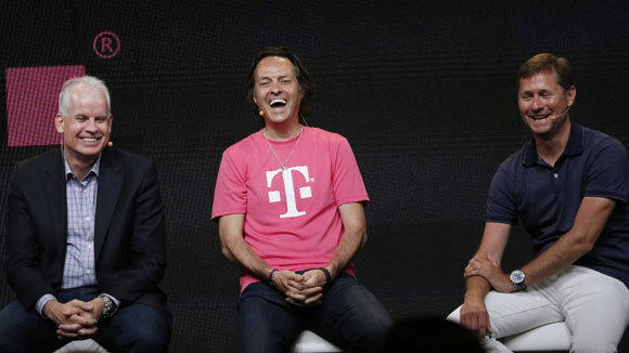 T- Mobile Chief Executive John Legere, center, laughs with other company executives at an event in New York Wednesday.