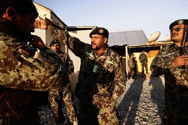 Afghan Lt. Col. Kohadamani Hamidullah instructs his men before a mission to look for Taliban weapons outside Maidan Shahr. His U.S. mentor is trying, inch by inch, to end Hamidullah's dependence on American military help.