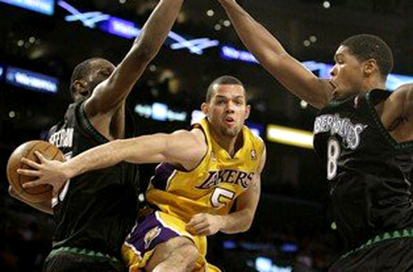 Jordan Farmar makes a no-look pass between Timberwolves defenders during a game with the Lakers in 2011.