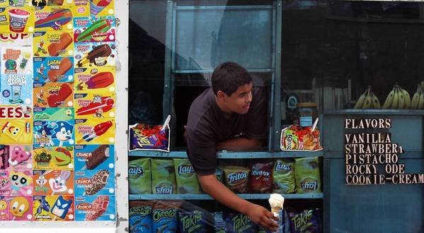 Felipe Hernandez, 15, helps his father serve ice cream from their truck in Long Beach. Some vendors have expressed concern about Long Beach's move to restrict ice cream truck music, saying the jingles are the only way to alert customers that their trucks are nearby.
