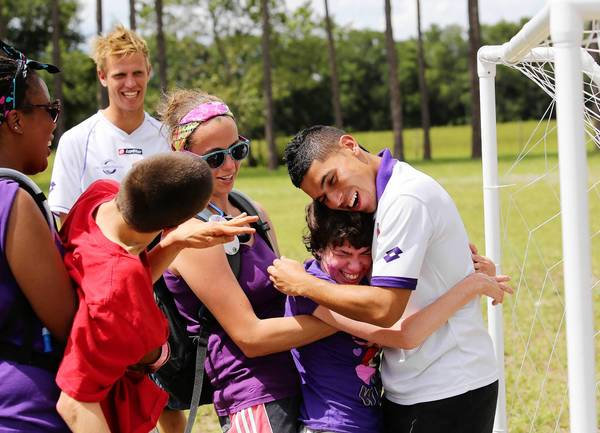 Members of the Orlando City Soccer Club's pro team hosted a soccer clinic at Camp Challenge in Rachel Nelson gets a hug from Orlando City's Johnny Mendoza.