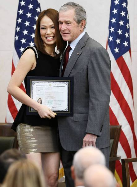 Former President George W. Bush poses with new U.S. citizen Phuong Quynh Ngyuyen during a citizenship ceremony at his presidential library in Dallas. In his comments at the event, Bush called upon Republicans to pass an immigration reform package.