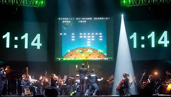 Tommy Tallarico conducts the score to 'Pong,' while a player plays the game in a 'Video Games Live' concert July 14.