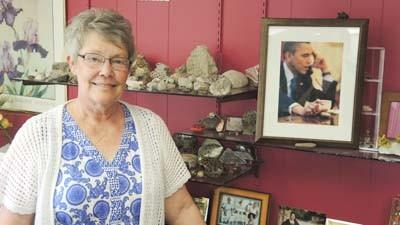 Bailey, the owner of Bailey's Place Petoskey Stones & Stuff, stands in front of Petoskey stone-filled shelves at her shop on U.S. 31 North. Also on display is a photograph showing President Barack Obama with a stone that was purchased at Bailey's Place.