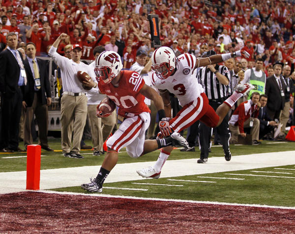 Wisconsin's James White scores a touchdown while being pursued by Nebraska quarterback Taylor Martinez in the first quarter.