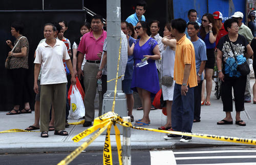 Residents and onlookers wait behind police tape near a five-story building that partially collapsed after a reported explosion in New York July 11, 2013. At least 10 people were injured when part of the building containing businesses and residences in Manhattan's Chinatown district collapsed after an explosion, fire officials said on Thursday. The cause of the explosion was not immediately clear, Fire Department Assistant Chief Robert Boyce said.