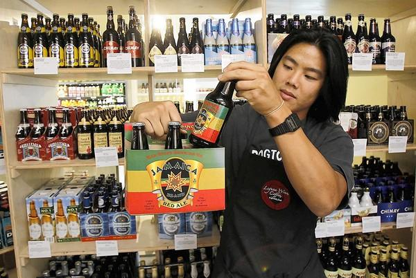 Clifton Huang shows off the popular Jamaican Red Ale from Red River Brewing Co. in the beer room at the new Laguna Wine, Coffee & Specialty Foods in downtown Laguna.