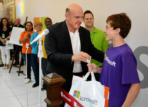 Microsoft CEO Steve Ballmer gives Justin Gudeman, 14, a gift bag containing a new Xbox game console during the grand opening of a company store in Troy, Mich.