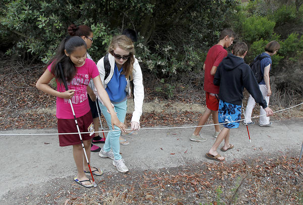 Braille Institute teen Veronica Sanchez, left, is led by Youth Assistant Katie Brazer as they begin oa hike of the Study Loop trail at Crystal Cove, Thursday.