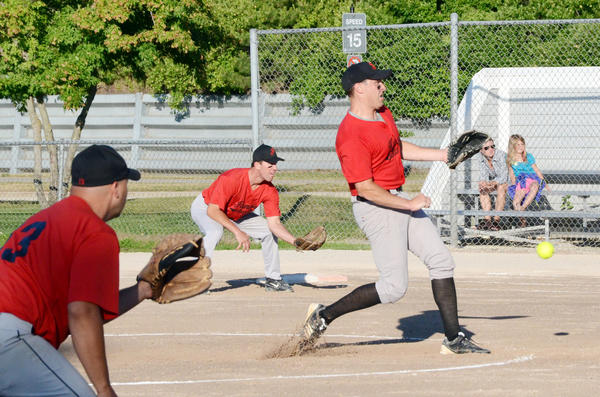 Colby Andrews (right) of Flynn's Excavating pitches as first baseman Todd Flynn (middle) and third baseman Jaime Barkley (letft) look on during Thursday's Petoskey Men's League contest with Dustin Memorial at Bayfront Park's Ed White Field. Flynn's defeated Dustin Memorial, 14-13, in eight innings.