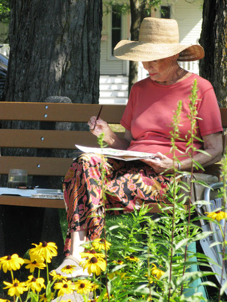 Beverly Eby does plein aire painting at the Charlevoix library.