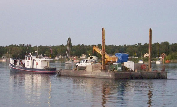A St. James Marine tug pulls a barge carrying the now-repaired engine for the Beaver Island ferry the Emerald Isle to the island Friday, July 12.