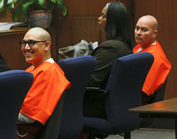 Rudy Ruiz, left, smiles while a relative of one of his victims makes a statement before he and his fellow defendant, John Perez, right, were sentenced to death for killing three people and wounding seven others in a Pico Rivera pizza parlor in 2009. At center is defense lawyer Cynthia Legardye.