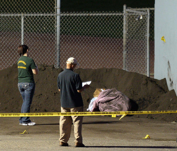 Investigators look over the scene where a body was found in a bag Thursday at a park in Manhattan Beach.