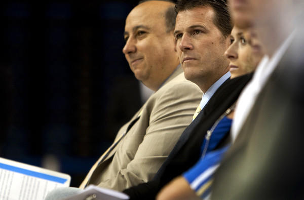 UCLA Athletic Director Dan Guerrero, left, and Steve Alford listen to a speaker during the introduction of Alford as the Bruins' new men's basketball coach.