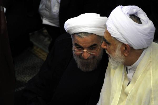 Iranian President-elect Hassan Rouhani, left, listens to a worshiper as they attend Friday prayers in Tehran. Some former top U.S. officials and foreign diplomats want the Obama administration to reach out to Iran to end the nuclear stalemate, but some analysts note that could spark a backlash from U.S. conservatives who think Rouhani is less moderate than he seems.