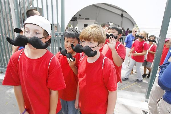 Youngsters from the Fountain Valley Unified School District summer camp wear giant mustaches as they enter the 2013 OC Fair on Friday.