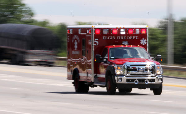 An Elgin ambulance leaves the scene of a medical incident near Route 20 and Shales Parkway in Elgin on July 10, 2013.