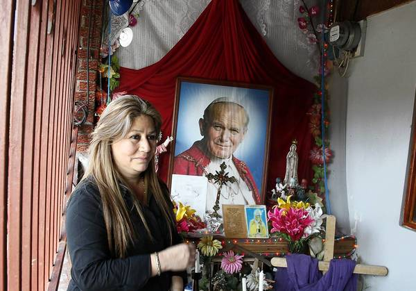 Costa Rica's Floribeth Mora stands by the shrine she made to Pope John Paul II at her. She suffered from a cerebral aneurysm that was inexplicably cured on May 1, 2011, the date of the late pope's beatification.