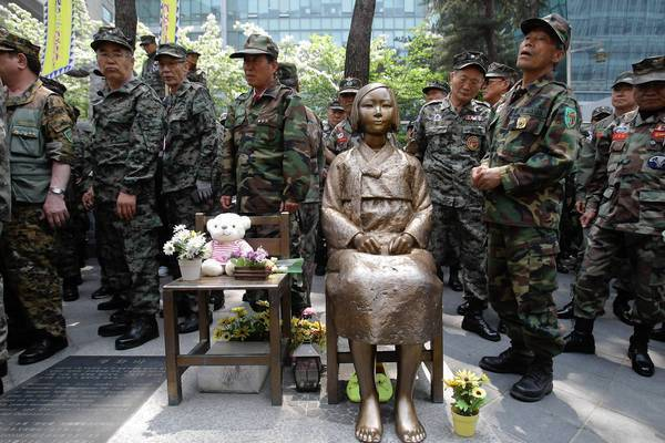 "South Korean Vietnam War veterans stand beside a statue honoring ""comfort women"" during a rally in front of the Japanese Embassy in Seoul. Remarks by the mayor of Osaka on the historic perception of ""comfort women,"" coerced into Japanese military brothels during World War II, have drawn intense criticism from neighboring countries and the United States."