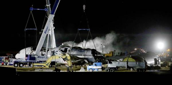 Asiana Airlines Flight 214 is dismantled and hauled to a hangar at San Francisco International Airport. More than 180 people were hurt when the plane crash-landed, and three girls have died.