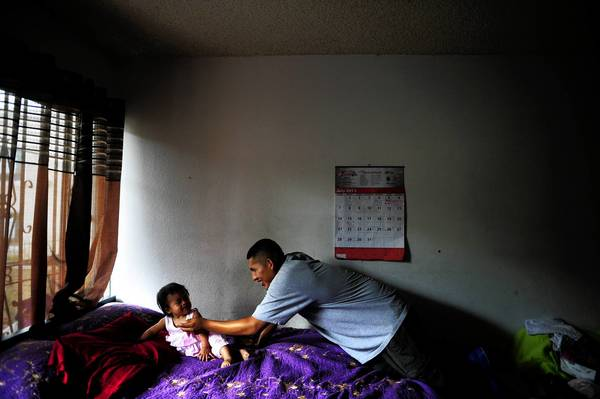 Frank Mariano, 16, a participant in the L.A. Fathers Program at Children's Hospital Los Angeles, plays with his 1-year-old daughter, Anabell, in their Koreatown home.