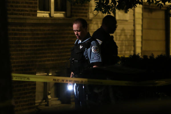 Police investigate the scene of a fatal shooting at Ridgeway Ave. and Le Moyne St early on July 13 (E. Jason Wambsgans/Chicago Tribune)