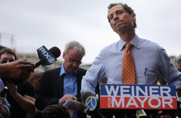 Anthony Weiner listens to a question from the media after courting voters outside a Harlem subway station a day after announcing he will enter the New York mayoral race.