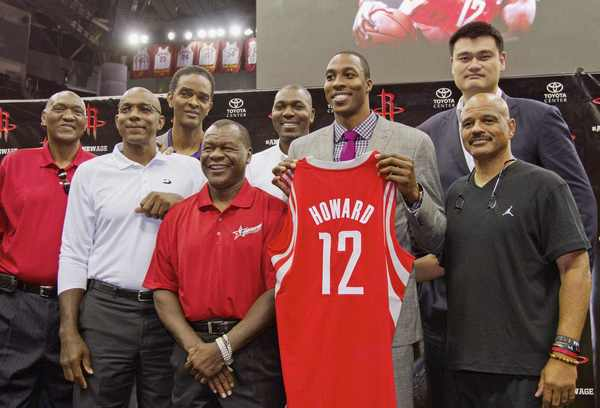 Dwight Howard holds his new Rockets jersey as he stands with former players (L-R) Elvin Hayes, Clyde Drexler, Ralph Sampson, Calvin Murphy, Hakeem Olajuwon, Yao Ming and John Lucas.