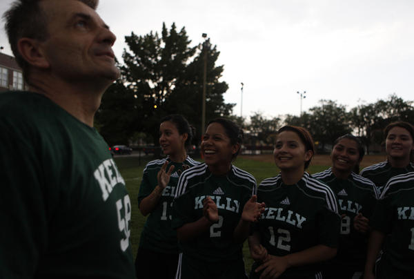 Kelly soccer coach Stan Mietus looks up at the stormy sky as the girls chant during practice.